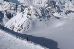 看下来在唯一滑雪轨道的滑雪者在朝向前下来 免版税库存图片