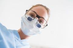 看下来在患者的手术口罩和牙齿寸镜的牙医 免版税库存照片