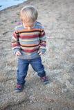 看下来在海滩的沙子的小男孩 免版税库存照片