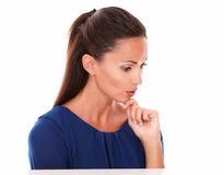 看下来用在下巴的手的友好的女孩 免版税库存照片