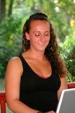 看下来膝上型计算机的微笑的青少年的女孩 库存照片