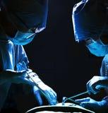 看下来,工作和拿着有患者的两位外科医生外科设备说谎在手术台上 免版税库存图片