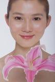 看与一朵大桃红色花的年轻平静的妇女画象照相机,演播室射击 库存照片
