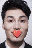 看与一面心形的中国旗子的年轻商人照相机盖他的嘴 库存图片