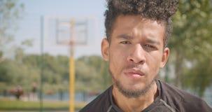 看与严肃的表示的年轻英俊的非裔美国人的男性篮球运动员特写镜头画象照相机 影视素材