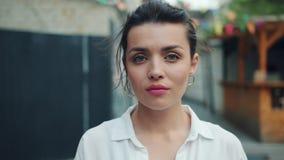 看与严肃的面孔的可爱的妇女画象照相机然后微笑 股票视频
