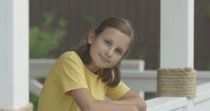 看与中立面孔的照相机和微笑对在红色的白色Terrasse射击的女孩画象 影视素材