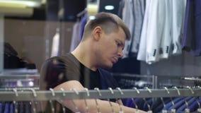 看与人的衣服的年轻可爱的人商店窗口在购物中心 影视素材