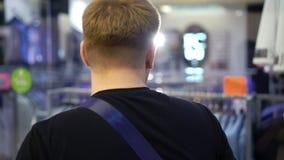 看与人的衣服的年轻可爱的人商店窗口在购物中心 股票视频