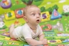 看与兴趣的五颜六色的背景的男婴 免版税库存照片