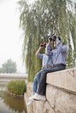 看与双筒望远镜的年轻夫妇,坐由运河 免版税图库摄影