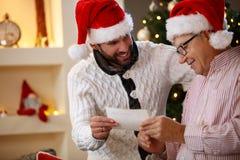 看与圣诞老人盖帽的孙子和祖父照片 免版税图库摄影