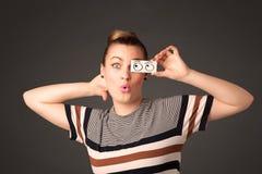 看与在纸的手拉的眼睛球的年轻傻的女孩 免版税库存照片