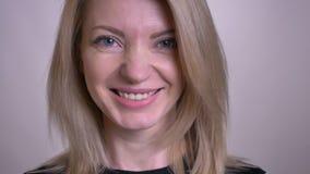 看与微笑的表情的成人有吸引力的白种人女性面孔特写镜头画象照相机与 股票录像