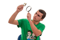 看与放大镜的年轻人一个胶片 免版税库存照片