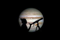 看与望远镜的女孩星 木星行星 免版税库存照片