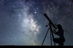 看与望远镜的女孩星 银河星系 免版税图库摄影