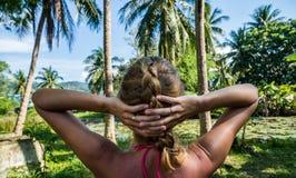 看与棕榈树和小池塘的妇女美好的热带看法 免版税库存照片