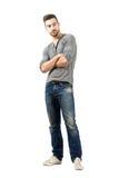 看与横渡的胳膊的牛仔裤的年轻人 库存照片