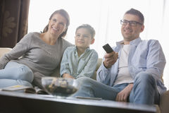 看与父母的男孩电视在客厅 免版税图库摄影