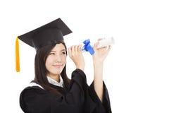 看与程度的微笑的毕业生妇女 免版税库存图片