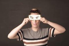 看与纸手拉的眼睛的凉快的年轻人 免版税库存图片