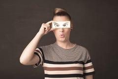 看与纸手拉的眼睛的凉快的年轻人 免版税图库摄影