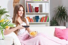 看与芯片的愉快的妇女电视 免版税库存照片