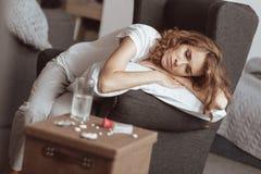 看与许多药片的沮丧的妇女桌 免版税库存图片