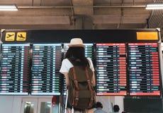 看与运载的亚裔妇女旅客信息板,手提箱 免版税库存图片