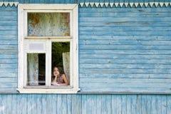 看乡间别墅窗口的哀伤的乏味小女孩倾斜她的面孔在她的手 库存图片