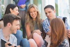 看书外面在校园里的愉快的学生 库存照片