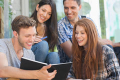 看书外面在校园里的愉快的学生 库存图片