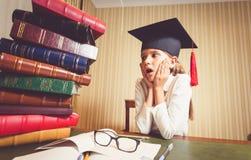 看书的大堆毕业盖帽的惊奇聪明的女孩 免版税库存图片