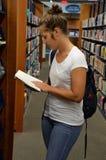 看书的女学生在图书馆里 图库摄影
