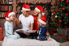 看书的家庭由圣诞节 免版税库存照片