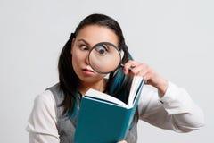 看书的滑稽的女孩通过放大镜 在灰色背景 免版税库存图片
