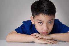看亚裔逗人喜爱的男孩画象哀伤和非常失望 免版税库存照片