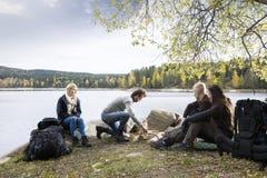 看人的朋友为在湖边野营的篝火做准备 库存照片