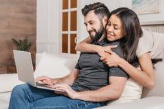 看人的非裔美国人的妇女在家键入在膝上型计算机 库存照片