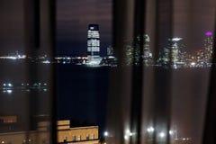 看从一看见的一种都市风景通过帷幕在晚上 库存照片