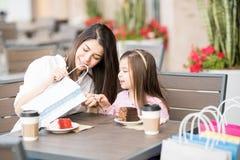 看他们在咖啡馆买的材料的母亲和女儿 免版税库存照片