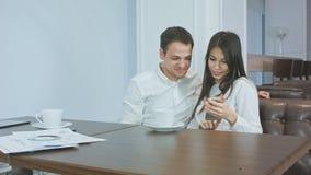 看他们的在电话和笑的咖啡馆的两个办公室工友照片 免版税库存照片