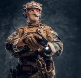 看伪装的制服的特种部队战士拿着有手电的一杆枪和斜向一边 演播室照片反对 库存照片