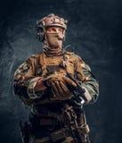 看伪装的制服的特种部队战士拿着有手电的一杆枪和斜向一边 演播室照片反对 免版税库存照片