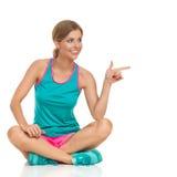 看体育的衣裳的妇女坐,指向和  库存照片