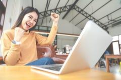 看便携式计算机的年轻可爱的亚裔妇女感觉愉快的快乐或激动的表示成功或胜利 免版税图库摄影