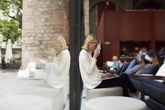 看便携式计算机scree与非饮料咖啡馆的确信的女商人 免版税库存图片