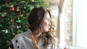 看俏丽的女孩坐在圣诞节装饰附近和在旁边 迟缓地 股票视频