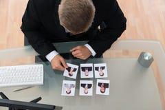 看候选人照片的商人 免版税图库摄影